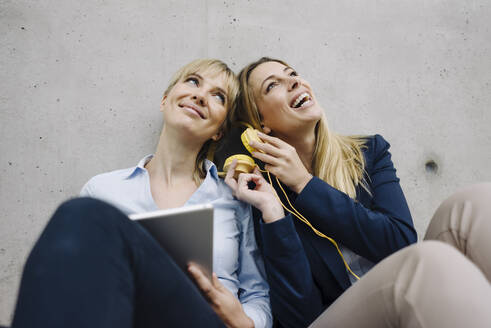Two happy young businesswomen sharing headphones - JOSF03874