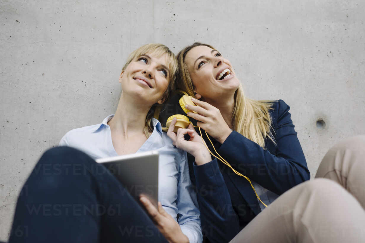 Two happy young businesswomen sharing headphones - JOSF03874 - Joseffson/Westend61