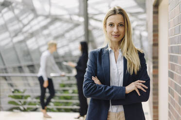 Portrait of a confident young businesswoman in a modern office building with colleagues in background - JOSF03880