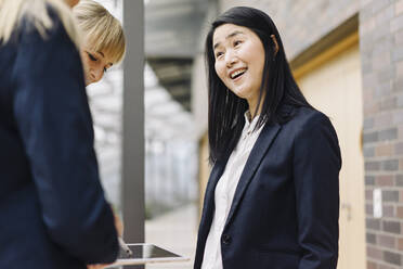 Portrait of happy businesswoman with colleagues in modern office building - JOSF03883