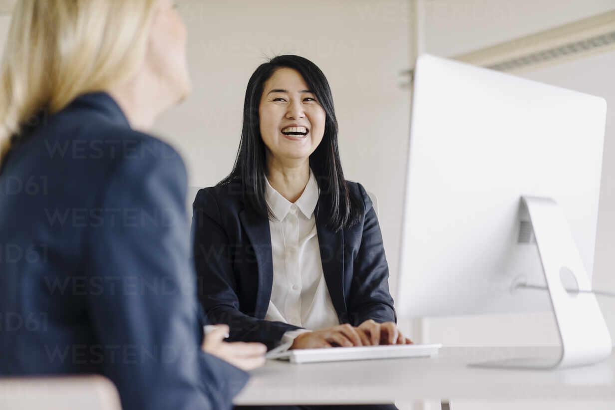 Two laughing businesswomen sitting at desk in office talking - JOSF03886 - Joseffson/Westend61