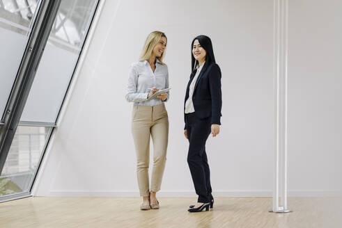 Two businesswomen with tablet standing in modern office - JOSF03889