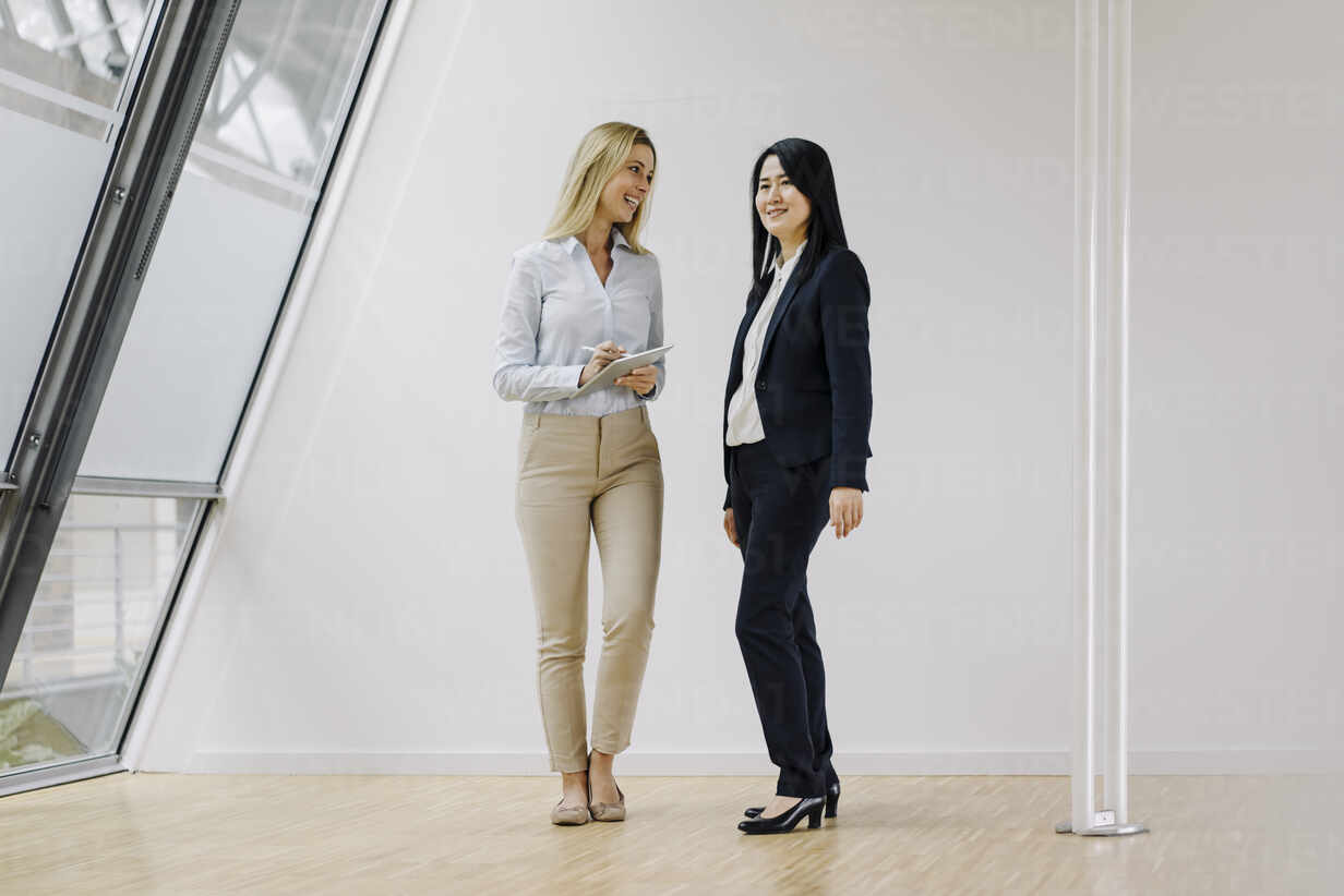 Two businesswomen with tablet standing in modern office - JOSF03889 - Joseffson/Westend61