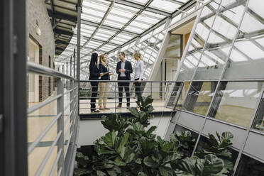 Business people standing on a skywalk in modern office building - JOSF03907