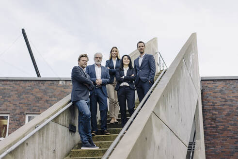 Portrait of confident business people on exterior stair - JOSF03943