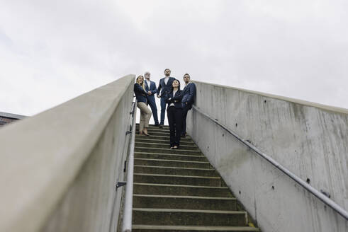 Business people standing on exterior stair looking out - JOSF03946