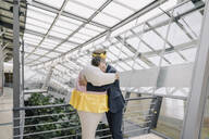 Businessman and man dressed up as a ballerina hugging in modern office building - JOSF03961