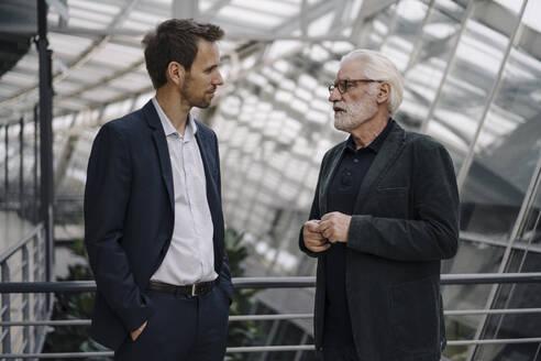 Two businessmen talking in modern office building - JOSF03964