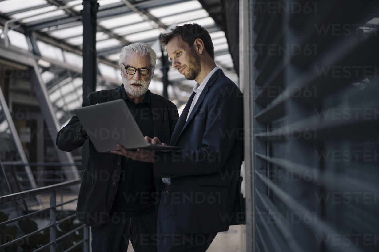 Two businessmen using laptop in office together - JOSF03967 - Joseffson/Westend61