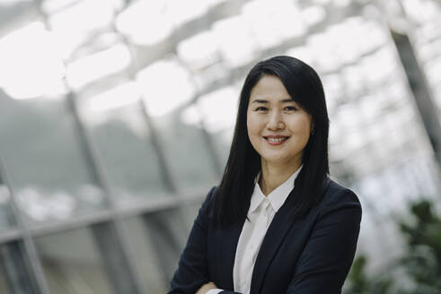 Portrait of a smiling businesswoman in a modern office building - JOSF03973