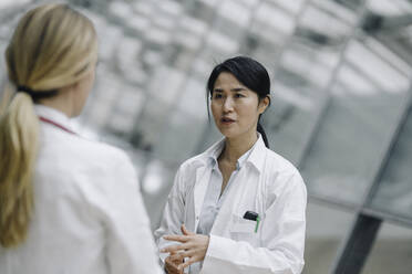 Female doctor talking to a colleague - JOSF03982