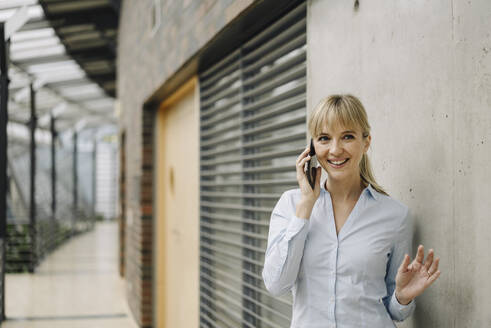 Portrait of a smiling young businesswoman on the phone - JOSF04015