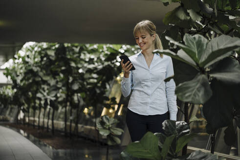 Smiling young businesswoman using cell phone in a modern office building surrounded by plants - JOSF04018