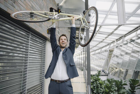 Cheerful businessman lifting up bicycle in modern office building - JOSF04033
