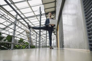 Businessman standing on one leg in modern office building using laptop - JOSF04036