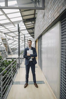 Businessman holding tablet in modern office building - JOSF04039