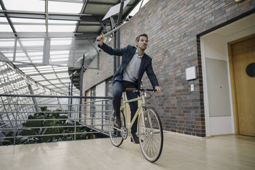 Businessman holding a toy sword and riding bicycle in modern office building - JOSF04042