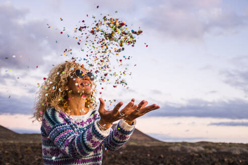 Happy blond woman throwing confetti in the air, Tenerife, Spain - SIPF02097
