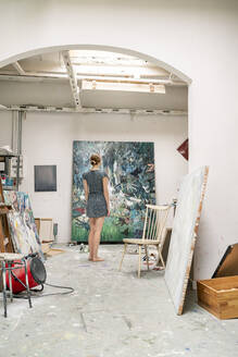 Young artist standing in her studio, looking at painting, rear view - PESF01741