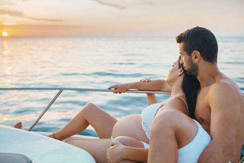 Romantic couple with pregnat woman sitting on boat - MIMFF00024