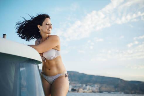 Woman in bikini enjoying the wind on a boat - MIMFF00027