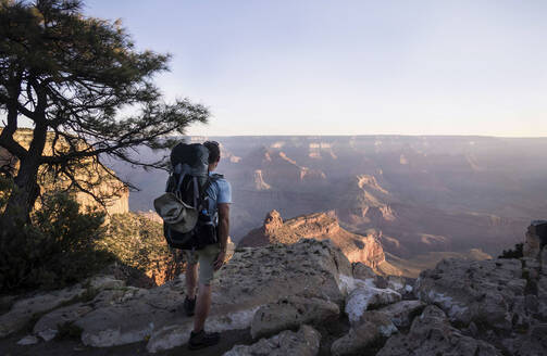 Rear view of man with backpack standing on mountain against at grand canyon - CAVF70310