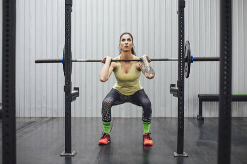 Confident woman lifting deadlift in gym - CAVF70417