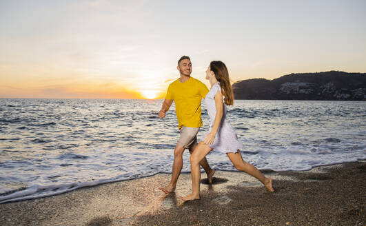 Young couple running at the beach during sunset - LJF01099