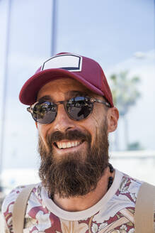 Smiling mature man with beard, red basecap and sunglasses - TCF06213