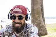 Mature man with red basecap, sunglasses and white headphones - TCF06231