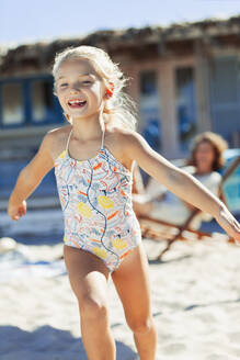 Carefree girl in bathing suit running on sunny beach - HOXF04501