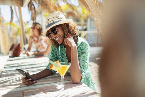 Happy young woman with smart phone drinking cocktail at sunny beach bar - HOXF04549