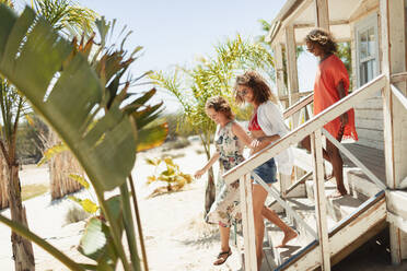 Women friends on sunny beach hut steps - HOXF04561