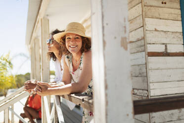 Portrait happy woman on sunny beach hut patio - HOXF04579