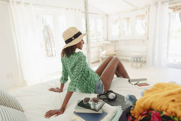 Woman relaxing on beach hut bed - HOXF04582