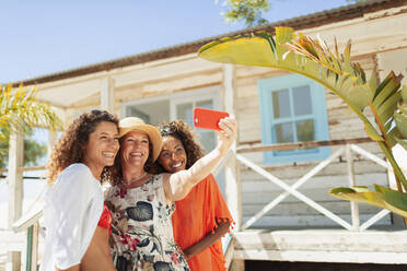 Happy mother and adult daughters taking selfie outside sunny beach hut - HOXF04600