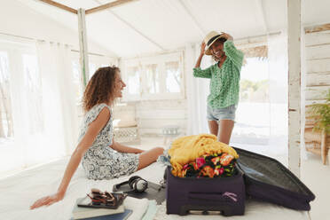 Young women friends unpacking suitcase in beach hut bedroom - HOXF04621