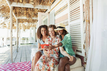 Happy mother and adult daughters taking selfie on beach hut patio - HOXF04624