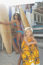 Portrait happy mother and daughter with surfboard and boogie board on sunny beach - HOXF04636