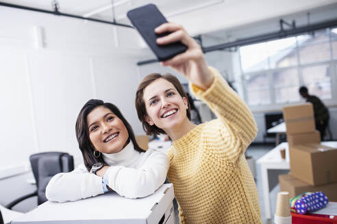 Smiling businesswomen taking selfie in new office - HOXF04825
