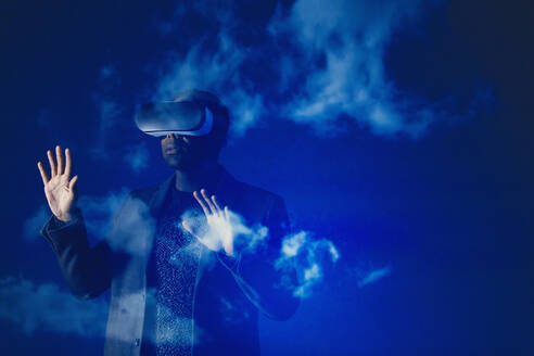 Double exposure businessman with virtual reality simulator glasses against blue sky with clouds - CAIF23398