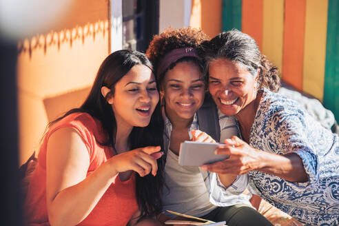 Happy mother and daughters taking selfie with smart phone - CAIF23500