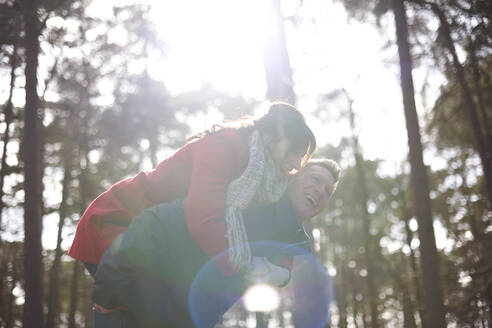 Happy, playful couple piggybacking in sunny, autumn woods - CAIF23527
