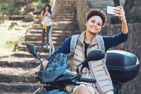 Young woman taking selfie with camera phone on motor scooter - CAIF23602