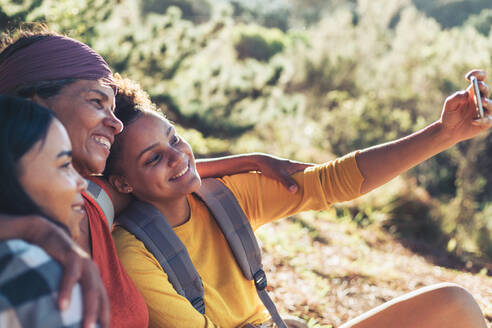Happy mother and daughter hikers taking selfie with camera phone - CAIF23605