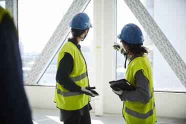 Side view of female engineers discussing at construction site - MASF15250