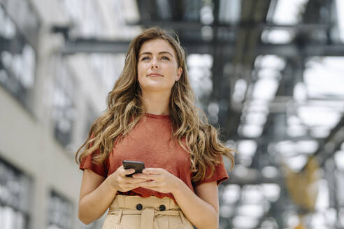 Portrait of smiling young brunette woman using smartphone, looking at distance - KNSF06945