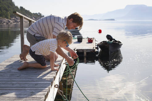 Father teaching son to tie boat to pier, Norway - CUF53999