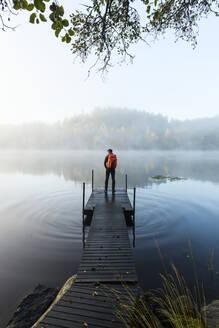 Man on pier in lake in morning fog - JOHF05023