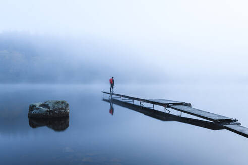 Man on pier in lake in morning fog - JOHF05026